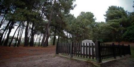El monolito y la valla ya restaurada en la fosa común del Pinar de Salinas, ayer. Mara Villamuza. LNE